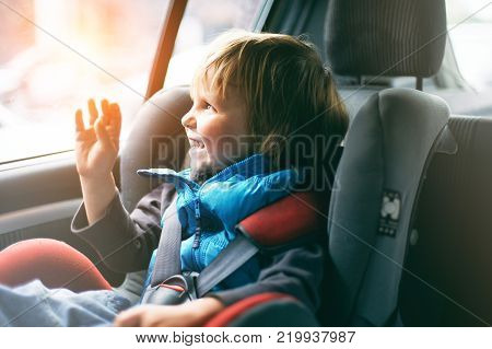 Portrait of pretty toddler boy sitting in car seat. Child transportation safety. Sunny day.