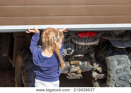 Little blond girl opening garage door where ATV stands. Back view.