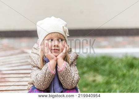 Portrait of young cute caucasian blond girl sitting on a bench in a park and thinking about smth with sorrow sad face. Wearing knitted hat, autumn.