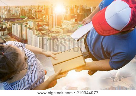 over head shot of woman receive container card box from delivery man against urban building and cargo - shipping plane background