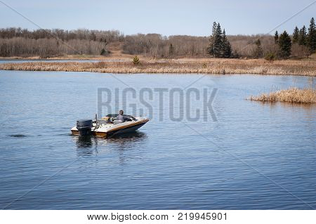 a man coasting along in his motorboat on a warm fall day.