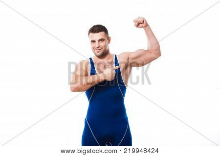 A young dark-haired man fighting Greco-Rican wrestling, the master of sports in grappling in a blue wrestling tights smiles and holds his hands in fists in a fighting pose against a white isolated background