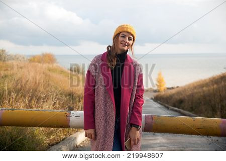 A dark-haired woman in a yellow knitted hat, a pink coat is standing on the path near the wheat field on an autumn  day, in the background of a birch tree with yellow leaves