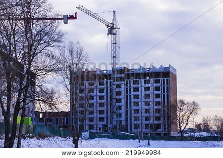 unfinished multi-storey house on the lake in winter