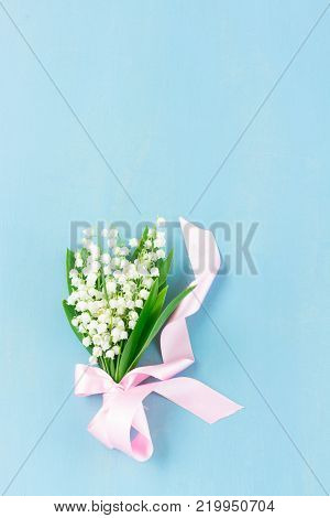 Lilly of the valley flowers on blue wooden background