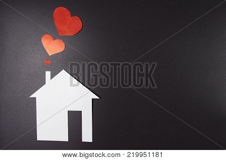 White paper house with red hearts from chimney on black background. Concept house. Insurance and safety of housing. Love, family and home