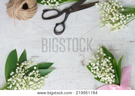 Lilly of the valley flowers with leaves frame on white wooden background