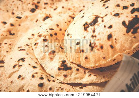 Roti or chapati making machine, selective focus. Indian ready to eat Indian flat bread coming out of machine
