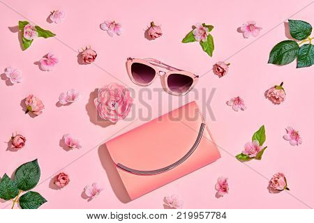 Fashion Woman Accessories Set. Pink Pastel Color. Flat lay. Minimal Style. Trendy fashion Floral Clutch, Glamour Summer Sunglasses. Roses Flowers. Spring Floral