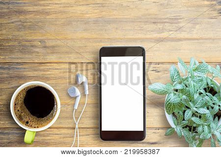 Smartphone white screen, white ear phone and cup of coffee on wooden table background, mockup modern smartphone jet black color.Top view with copy space for use.