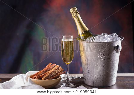 Champagne Bottle In Bucket With Ice And Glasses Of Champagne On Dark Background