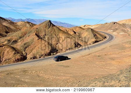Death Valley National Park, California, USA - November 23, 2017. One-way Artists Drive road in the Death Valley National Park in USA, with car.