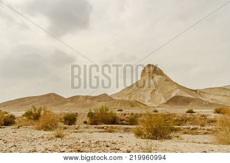 Landscape scenic view on rock and sand in dry desert in Israel. Hot middle east wilderness. Scenic outdoor view on wild land. Summer heat and sunlight, nobody on photo