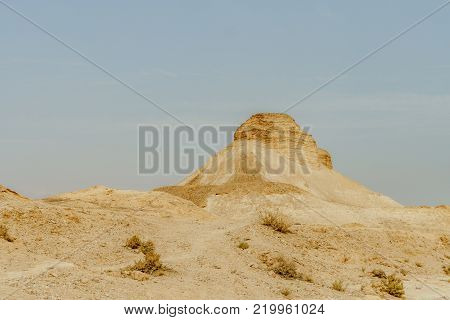 Landscape scenic view on rock in dry desert in Israel. Sand, rocks and stones in hot middle east wilderness. Scenic outdoor view on wild land. Summer heat and sunlight, nobody on photo
