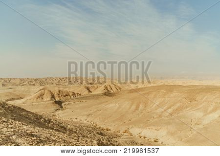 Landscape of mountain hill dry desert in Israel. Valley of sand, rocks and stones in hot middle east tourism place. Scenic outdoor view on wild land. Summer heat and sunlight with nobody on photo