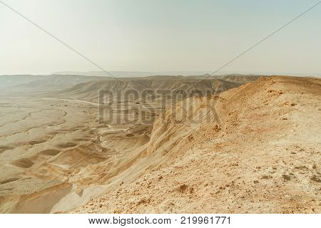 Landscape of view from canyon dry desert in Israel. Valley of sand, rocks and stones in hot middle east tourism place. Scenic outdoor view on wild land. Summer heat and sunlight with nobody on photo