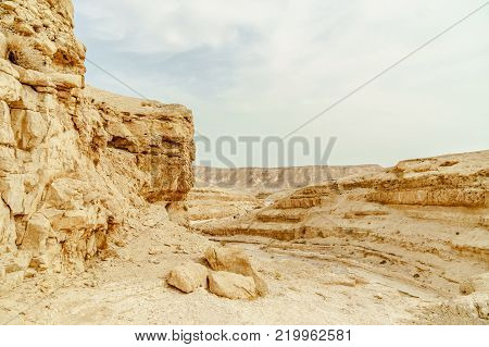 Landscape of dry and wild desert in Israel. Valley of sand, rocks and stones in hot middle east tourism place. Scenic outdoor view on wild land. Summer heat and sunlight with nobody on photo