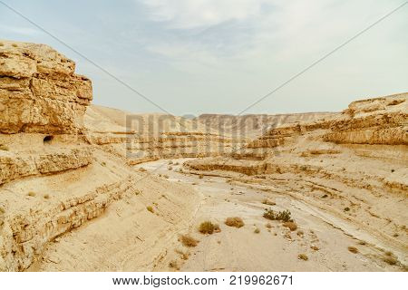 Summer scenic landscape view on dry desert in Israel. Valley of sand, rocks and stones in hot middle east tourism place. Scenic outdoor view on wild land. Summer heat and sunlight, nobody on photo