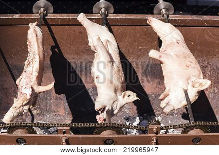 three pork skewered on an iron cooking on some embers in a market on the street