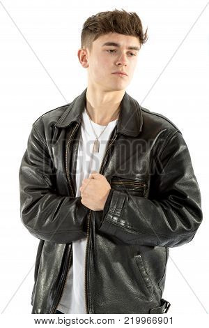 18 year old reaching inside his leather jacket isolated on white background
