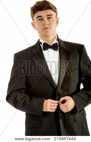 18 year old wearing a tuxedo doing up his jacket isolated on a white background