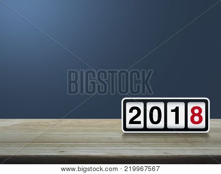 Retro flip clock with 2018 text on wooden table over light blue gradient background, Happy new year concept