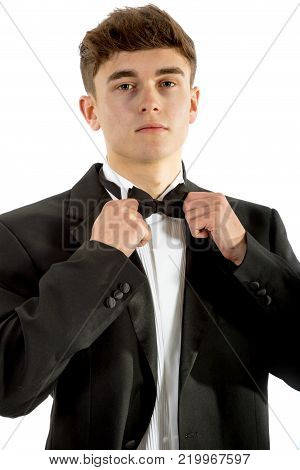 18 year old wearing a tuxedo adjusting his bowtie isolated on a white background