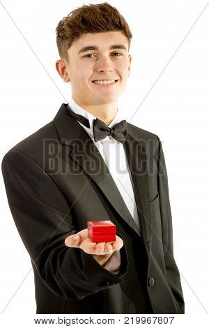 18 year old wearing a tuxedo smiling with a ring box isolated on a white background