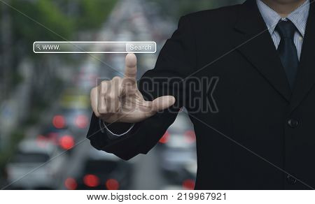 Businessman hand pressing search www button over blur of rush hour with cars and road, Searching system and internet concept