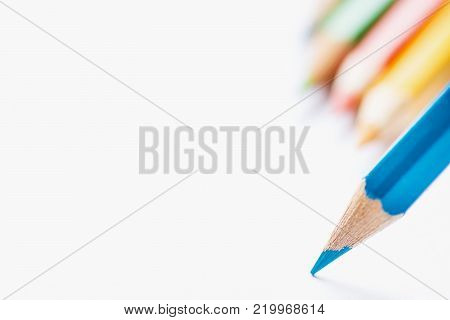 Row of Multicolored Pencils in Background Single Blue Sharp Pencil Pointing with Tip to Blank White Paper. Beginning of Drawing. Creativity Graphic Design Crafts Kids School Concept. Copy Space