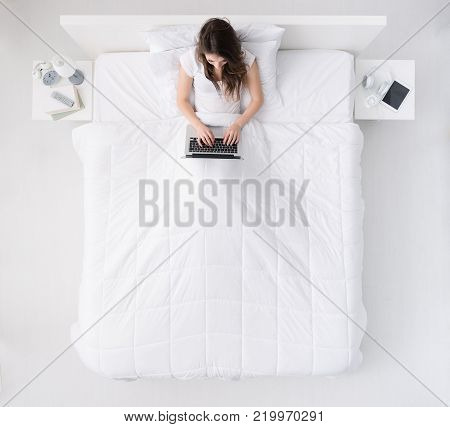 Sad frustrated woman in bed, she is covering her ears with a pillow, insomnia or noise concept, top view