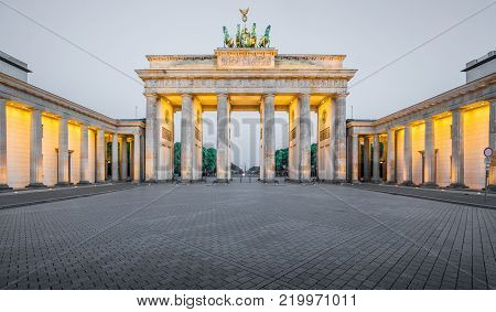 Classic panoramic view of historic Brandenburg Gate, Germany's most famous landmark and a national symbol, in post sunset twilight during blue hour at dusk in summer, central Berlin, Germany