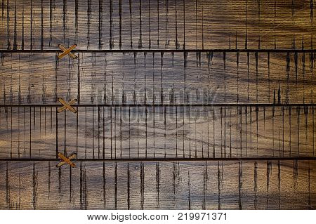 Old vintage brashed wooden boards connected in one wide by leather cross junctions.