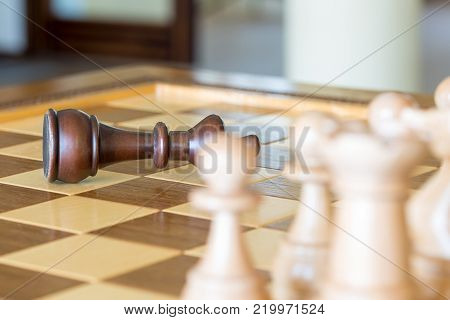 Beautiful wooden chess figures on a wooden luxury chessboard at the lounge area. Dark king is defeated.