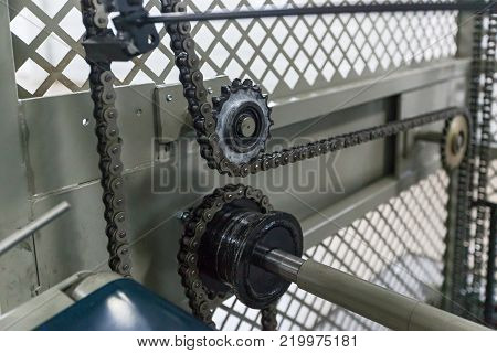 Triple strand roller chain going around three sprockets on industrial machine. the chain drive shaft Line Conveyor Industrial