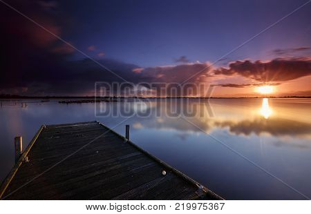 Wooden platform in early sunlight in a calm lake with blue sky and pink clouds