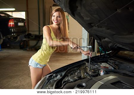 A Girl Is Holding Tools While Repairing A Car With An Open Hood In The Garage. The Girl With A Dazzl