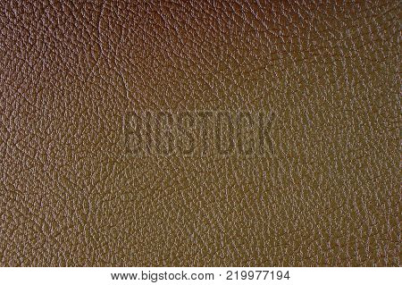 Texture of artificial leather. Brown background or leatherette backdrop.