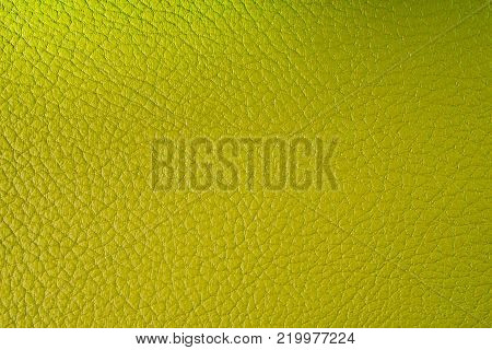 Texture of artificial leather. Lemon background with reflection of light or backdrop of leatherette.