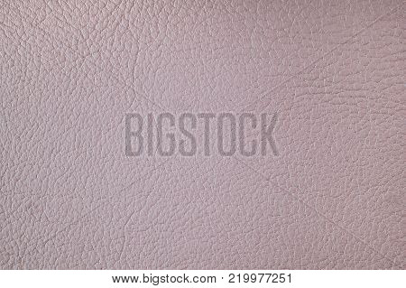 Texture of artificial leather. Pale pink background with a glint of light or a backdrop of leatherette.