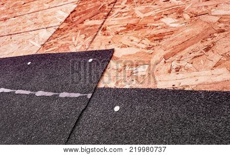 Closeup of overlapping black asphalt shingles and underlying oriented strand board subroof material