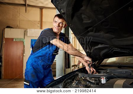 An Auto Mechanic In A Dirty Work Uniform Repairs A Car In The Garage. The Bonnet Is Open, The Guy Lo