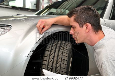 Car insurance expert, inspecting car front damage.