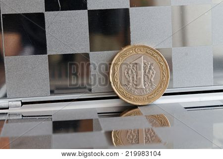 Turkish coin in mirror reflect wallet lies on wooden bamboo table background Denomination is one lira