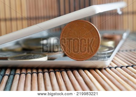 Pile of Euro coins in mirror reflect wallet lies on wooden bamboo table background Denomination is 5 euro cents - back side