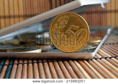 Pile of Euro coins in mirror reflect wallet lies on wooden bamboo table background Denomination is fifity euro cents
