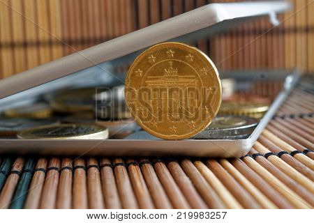 Pile of Euro coins in mirror reflect wallet lies on wooden bamboo table background Denomination is 20 euro cents - back side