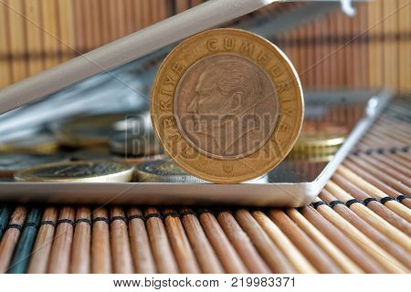 Turkish coins in mirror reflect wallet lies on wooden bamboo table background Denomination is 1 lira - back side