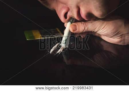 Junkie Is Snorting Cocaine Powder With Rolled Banknote.