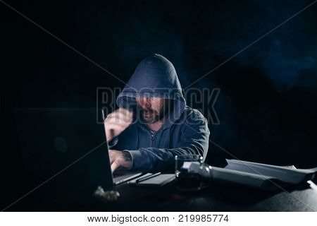 a mysterious criminal man does something illegal on a laptop, a hacker, in the dark